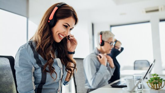 RingCentral-Woman with red headset smiling at desk